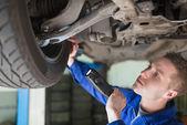 Meccanico esaminando pneumatico — Foto Stock