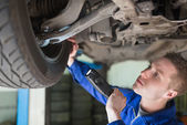 Mechanic examining tire — Stock Photo