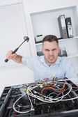 Portrait of frustrated man hitting cpu with hammer — Stock Photo