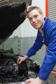 Auto mechanic checking car engine oil — Stock Photo
