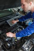 Mechanic with tablet pc repairing car — Foto de Stock