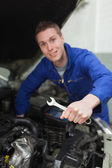 Mechanic with spanner repairing car — Stock Photo