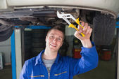 Mechanic repairing car with adjustable pliers — Stock Photo