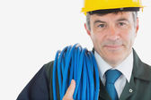 Repairman with rolled wire wearing hardhat — Stock Photo