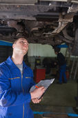 Mechanic under car writing on clipboard — Stock Photo