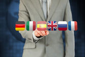 Businessman's finger activating state flags on touchscreen — Stock Photo
