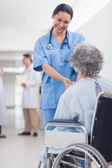 Doctor greeting recovering senior patient in wheelchair — Stock Photo