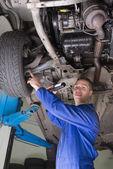 Male mechanic examining under vehicle — Stock Photo