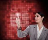 Businesswoman standing against a red background — Stock Photo