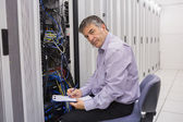 Technician looking up from making notes on server — Stock Photo