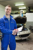 Happy auto mechanic writing on clipboard — Stock Photo