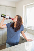 Woman drinking wine straight out of the bottle — Stock Photo