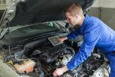 Mechanic with digital tablet repairing car engine — Stock Photo