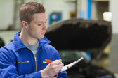 Mechanic writing on clipboard — Stock Photo