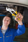 Mechanic repairing car with pliers — Stock Photo