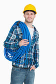 Portrait of smiling male architect carrying coiled blue tubing — Stock Photo