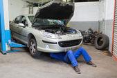 Hombre mecánico trabajando bajo auto — Foto de Stock
