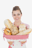 Young maid holding bread basket — Stock Photo