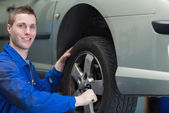 Happy mechanic changing car tyre — Stock Photo