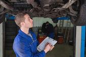 Mechanic under car preparing checklist — Stock Photo