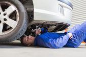 Auto mechanic under car — Stock Photo