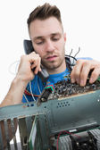 Computer engineer working on sound card on cpu while on call — Stock Photo