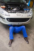 Male mechanic lying under car — Stock Photo