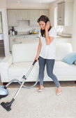Woman standing holding a vacuum cleaner wearing headphones — Stock Photo