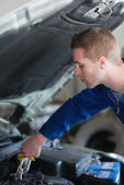 Car mechanic adjusting engine — Stock Photo