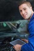 Mechanic holding digital tablet — Stock Photo