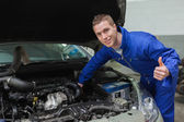 Mechanic under car bonnet gesturing thumbs up — Stock Photo