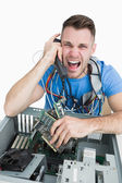 Frustrated computer engineer screaming over the phone in front o — Stock Photo