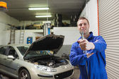 Mechanic offering spanner in worshop — Stock Photo