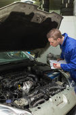 Mechanic with clipboard examining car engine — Stock Photo