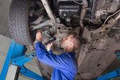 Repairman examining under car — Stock Photo