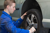 Male mechanic changing car wheel — Stock Photo