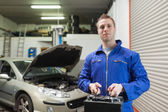 Mechanic carrying car battery — Stockfoto