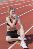 Woman sitting on running track and drinking — Stock Photo
