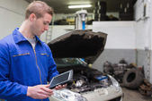 Mechanic with digital tablet at garage — Stock Photo