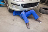 Mechanic working under car — Stock Photo