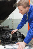 Mechanic checking car engine oil — Stock Photo