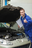 Mechanic by car showing thumbs up — Stock Photo