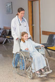 Doctor wheeling a patient in a wheelchair — Stock Photo