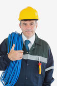 Confident male repairman with rolled wire and hardhat — Stock Photo