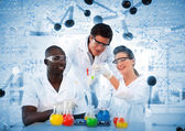 Smiling chemists looking at test tube — Stock Photo