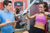Trainer noting progress of woman using weights machine — Stock Photo