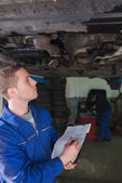Mechanic with clipboard examining car — Stok fotoğraf