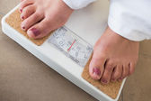 Womans feet on scales — Stockfoto
