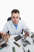 Portrait of confused computer engineer with cpu parts — Stock Photo