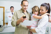 Family looking at medicine and a prescription in a pharmacy — Stock Photo